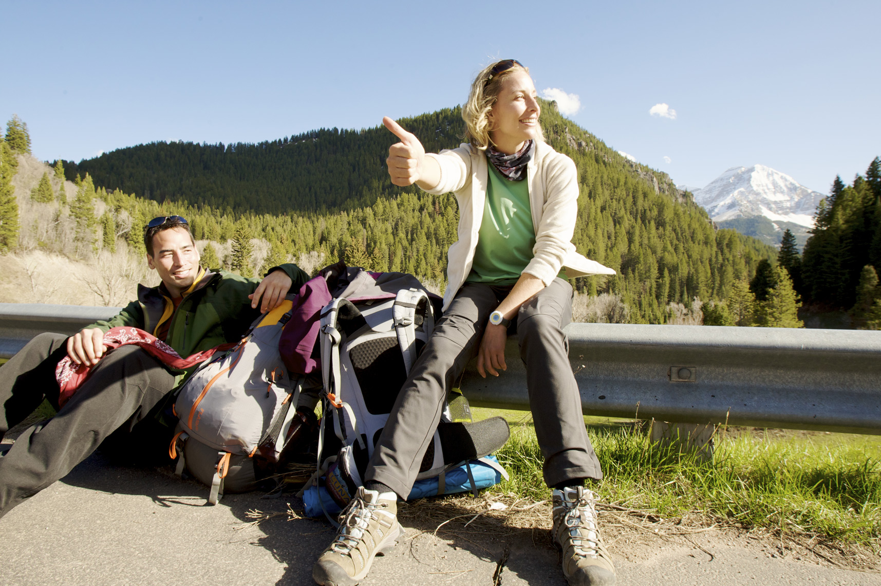 Couple of hikers hitchhiking in Utah after a trip in the backcountry/Steve Mason Photography